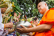 "22 JULY 2013 - PHRA PHUTTHABAT, THAILAND: A monk receives flowers from the crowd during the Tak Bat Dok Mai at Wat Phra Phutthabat in Saraburi province of Thailand, Monday, July 22. Wat Phra Phutthabat is famous for the way it marks the beginning of Vassa, the three-month annual retreat observed by Theravada monks and nuns. The temple is highly revered in Thailand because it houses a footstep of the Buddha. On the first day of Vassa (or Buddhist Lent) people come to the temple to ""make merit"" and present the monks there with dancing lady ginger flowers, which only bloom in the weeks leading up Vassa. They also present monks with candles and wash their feet. During Vassa, monks and nuns remain inside monasteries and temple grounds, devoting their time to intensive meditation and study. Laypeople support the monastic sangha by bringing food, candles and other offerings to temples. Laypeople also often observe Vassa by giving up something, such as smoking or eating meat. For this reason, westerners sometimes call Vassa the ""Buddhist Lent.""     PHOTO BY JACK KURTZ"