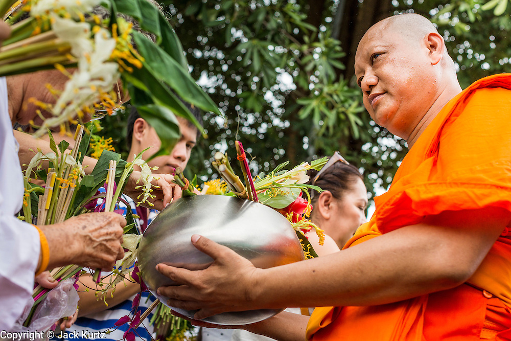 """22 JULY 2013 - PHRA PHUTTHABAT, THAILAND: A monk receives flowers from the crowd during the Tak Bat Dok Mai at Wat Phra Phutthabat in Saraburi province of Thailand, Monday, July 22. Wat Phra Phutthabat is famous for the way it marks the beginning of Vassa, the three-month annual retreat observed by Theravada monks and nuns. The temple is highly revered in Thailand because it houses a footstep of the Buddha. On the first day of Vassa (or Buddhist Lent) people come to the temple to """"make merit"""" and present the monks there with dancing lady ginger flowers, which only bloom in the weeks leading up Vassa. They also present monks with candles and wash their feet. During Vassa, monks and nuns remain inside monasteries and temple grounds, devoting their time to intensive meditation and study. Laypeople support the monastic sangha by bringing food, candles and other offerings to temples. Laypeople also often observe Vassa by giving up something, such as smoking or eating meat. For this reason, westerners sometimes call Vassa the """"Buddhist Lent.""""     PHOTO BY JACK KURTZ"""