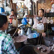 NYAUNG-U, Myanmar - A woman measures out cooking oil for a customer at Nyaung-U Market, near Bagan, Myanmar (Burma).