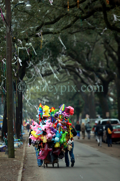 04 March 2014. New Orleans, Louisiana.<br /> Fat Tuesday. Mardi Gras Day. Trinket sellers prepare for the day along St Charles Avenue.<br /> Photo; Charlie Varley/varleypix.com