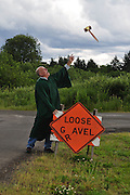 """Humorous photograph of a man dressed like a judge looking up in the air at a gavel while standing next to a LOOSE GRAVEL temporary traffic control sign that has been changed to read LOOSE GAVEL by dropping the """"R""""."""