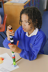 Primary school girl counting using unilink blocks in practical maths lesson,