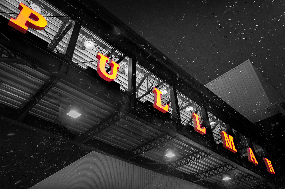 A large neon sign adorns the walkway connecting the parking garage with Pullman Square as snow fills the air in Huntington, West Virginia.