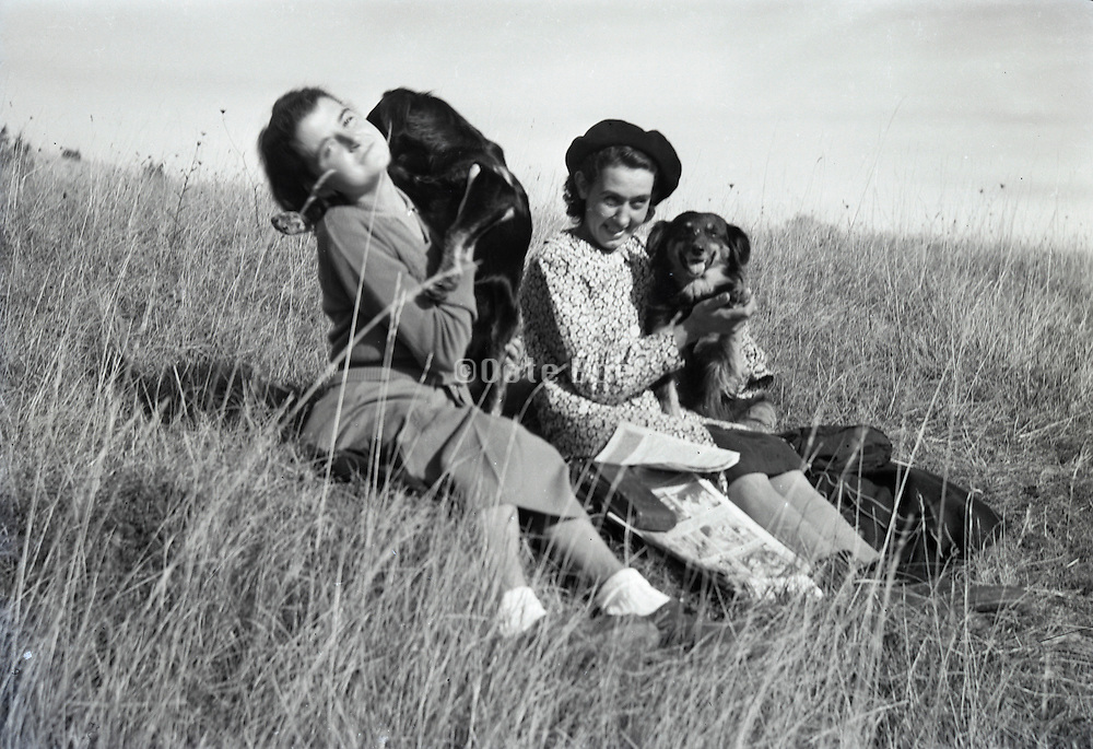 two young adult girls each with a dog sitting