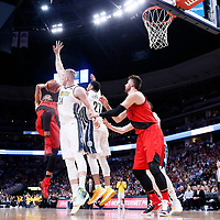 09 April 2018: Portland Trail Blazers guard CJ McCollum (3) takes a jump shot over Denver Nuggets center Mason Plumlee (24) and Denver Nuggets guard Jamal Murray (27) during the Denver Nuggets 88-82 victory over the Portland Trail Blazers, at the Pepsi Center, Denver, Colorado, USA.