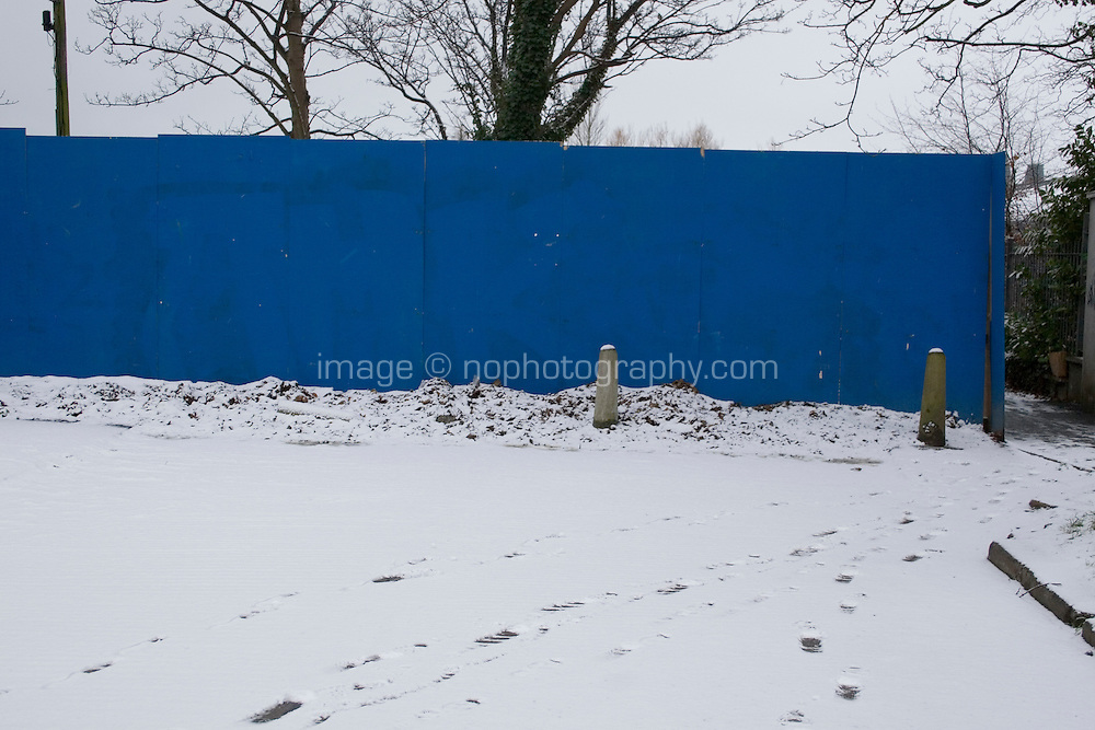 Snow covered path with blue hording in suburban in Dublin Ireland