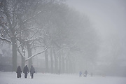 Walkers brave freezing temperatures in their local London park. During a prolonged cold spell of bad weather, snow fell continuously on the capital days before, allowing families the chance to enjoy the bleak conditions in Ruskin Park in the borough of Lambeth. Freezing fog also hampered any sun from thawing the fresh snow, keeping temperatures below zero. The branches of 100 year-old ash trees are seen bare above and in the distance over Edwardian period homes.