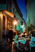 People sitting at resturant tables in the evening light, 23rd July 1989, Arles, France.