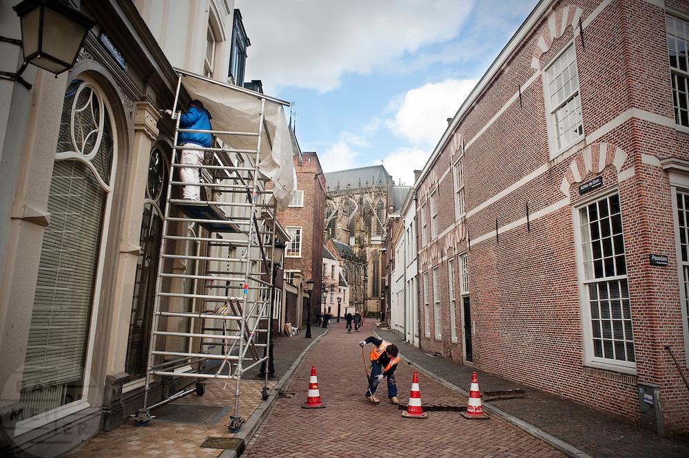 Een schilder staat onder een zelfgemaakte afdak te schilderen, terwijl een stratenmaker een gleuf aan het maken is voor werkzaamheden