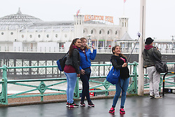 © Licensed to London News Pictures. 02/06/2015. Brighton, UK. A group of girls taking a selfie. Brighton and the South Coast are being battered by strong wind and big waves. The Lifeguard Service has raised the red flag advising people to stay out the water. today June 2nd 2015. Photo credit : Hugo Michiels/LNP