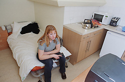 Female resident watching television in 'moveon' resettlement flat in homeless hostel,