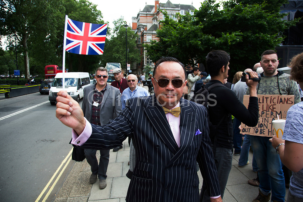 Pin striped suit protester waves his Union Jack flag at College Green in Westminster outside the Houses of Parliamant following a Leave vote, also known as Brexit as the EU Referendum in the UK votes to leave the European Union on June 24th 2016 in London, United Kingdom. Membership of the European Union has been a topic of debate in the UK since the country joined the EEC, or Common Market in 1973. It will be the second time the British electorate has been asked to vote on the issue of Britains membership: the first referendum being held in 1975, when continued membership was approved by 67% of voters. The two sides are the  Leave Campaign, commonly referred to as a Brexit, and those of the Remain Campaign who are also known as the In Campaign.
