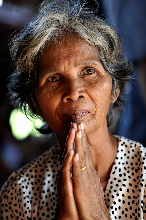 Member of a self-help group in the Phnom Penh neighborhood of Sen Rikreay, Thorng Noun, 59, listens raptly as a Buddhist monk addresses the group. Many people in this community are infected or affected by HIV and AIDS, and Buddhist monks and other religious meet with them regularly to mediate and discuss their challenges.