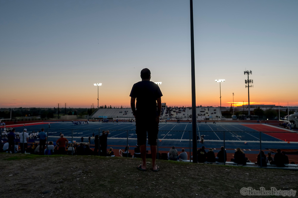 A fan watches the game from outside the stadium during the JV game as the Folsom High School Bulldogs varsity football team host the Oak Ridge High School Trojans,  Friday Nov 4, 2016.<br /> photo by Brian Baer