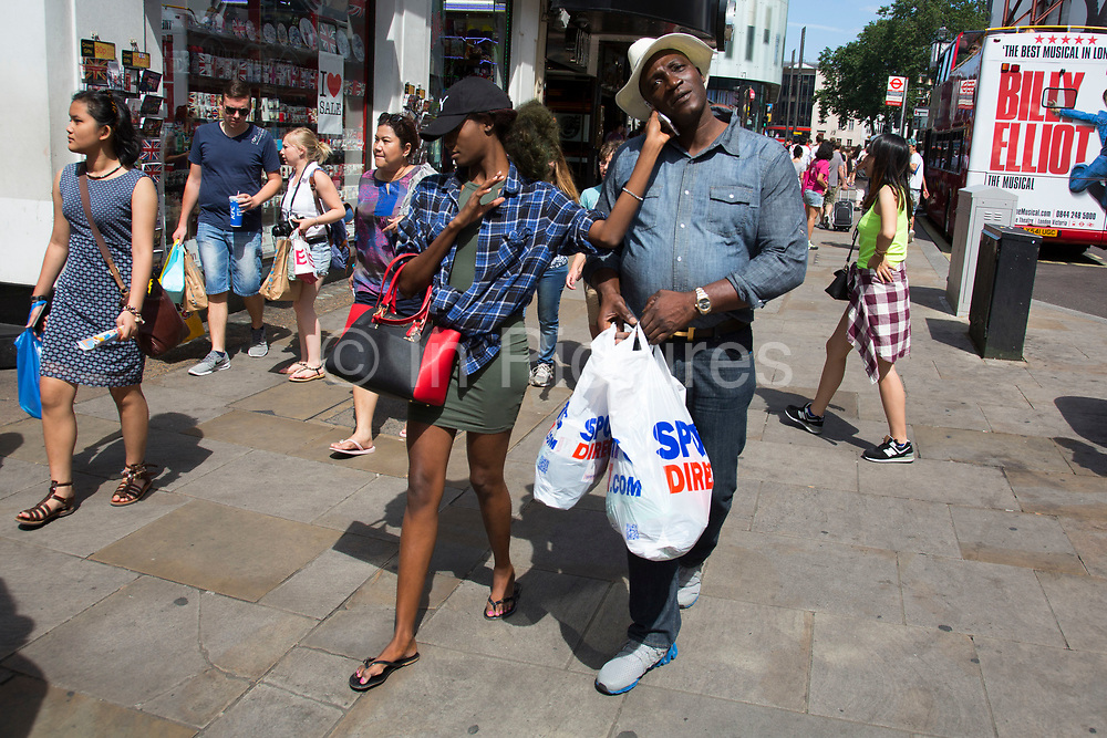 Summertime in London, England, UK. Crowds of tourists and shoppers gather in Leicester Square. This remains one of London's tourism hot spots with entertainers and shop and space to hang out. Woman holding up a mobile phone to the ear of her shopping partner while his hands are full of bags.