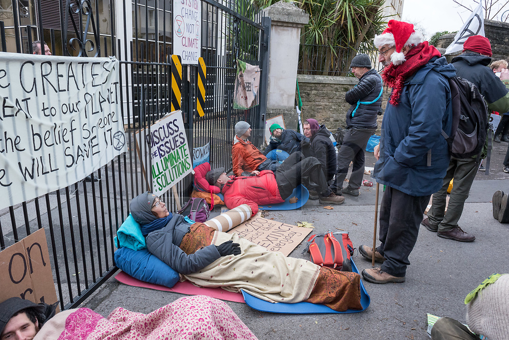 © Licensed to London News Pictures. 21/12/2018. Bristol, UK. 'Extinction Rebellion' campaigners block the side entrance and car park at the BBC Bristol offices in Whiteladies Road after three campaigners locked themselves together blocking the main entrance while others sang modified christmas carols on the shortest day just before Christmas to draw attention to the catastrophic impact of climate change. Campaigners later left peacefully without arrest. The Extinction Rebellion campaign says there will be mass actions outside the main BBC headquarters in London, Manchester, Norwich and Bristol to bring to light what they say is the utter failure of the BBC to fulfill their most fundamental duty to educate and inform the British public on the most important issue of our time, the climate crisis.<br /> Extinction Rebellion say the BBC must lead from the front on the climate emergency and make these demands: 1: The BBC Director General Tony Hall to agree to a meeting with a delegation from Extinction Rebellion to discuss how the corporation can meet its crucial moral duty to tell the full truth on the climate and ecological emergency. 2: The BBC to declare a climate and ecological emergency that we need to act now, the extinction of the natural world is happening and we face the collapse of our civilisations.3: That the BBC place the climate and ecological emergency as its top editorial and corporate priority - integrated into all of aspects of the BBC's output, not just environmental sections - by adoption of a climate emergency strategic plan, at the level of urgency the corporation placed on informing the public about World War 2. 4: The BBC to divest all pension funds, investments and bank accounts from fossil fuel corporations and their bankers. 5: The BBC, its subsidiaries and its supply chain to agree to be zero-carbon by 2025. 6: The BBC to publish an annual eco-audit of all BBC operations, including summary of key ecological and carbon data. 7: The BBC to take