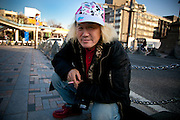 TOKYO, JAPAN - 10 MARCH - Harajuku - 2010 - Toshikazu KAN is about 60 year old. He wears clothe as a teenagers of harajuku, Pink michey cap, Pink cigaret, and blond hair style. He comes every weeks in harajuku. March 2010