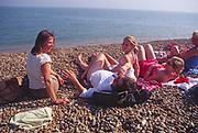AYBR67 Woman friends and children sunbathe and chat on shingle beach summer England