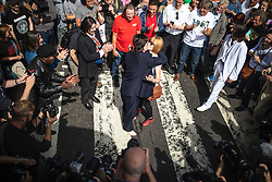 © Licensed to London News Pictures. 08/08/2019. London, UK. Paul McCartney (real name Joe Kane) from The Beatles tribute band 'Fab Four' proposes on the zebra crossing outside the Abbey Road studios in north London. The Beatles were photographed for the Abbey Road album cover 50 years ago today by Iain Macmillan. Photo credit: Rob Pinney/LNP