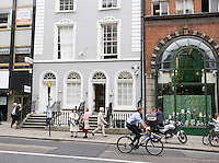 People waiting at bus stop and a cyclist on Dawson Street in Dublin Ireland