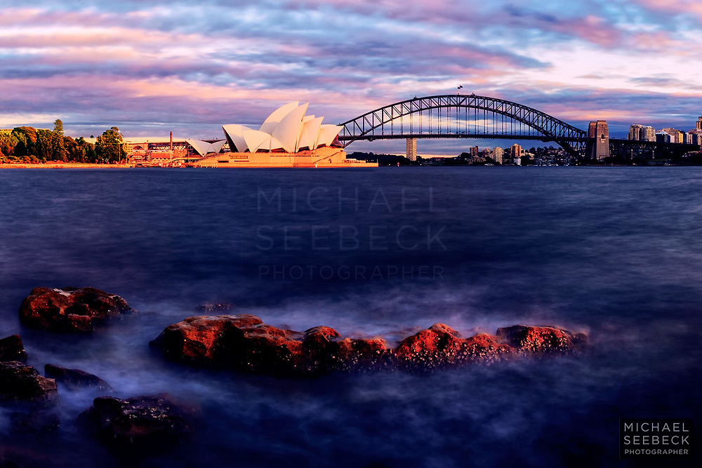 Small waves wash over rocks in the foreground, with Sydney Opera House and Sydney Harbour Bridge in the distance.<br /> <br /> Code: LANM0002<br /> <br /> Limited Edition Print