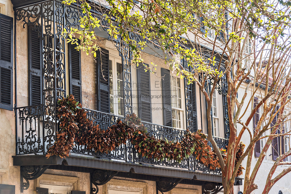 Magnolia Christmas roping decorates the wrought iron balcony of a historic home decorated on Church Street in Charleston, SC.