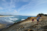 Kids playing on sand dune in Pacific City, OR