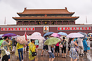 Tourists sheltering under umbrellas walk past the Gate of Heavenly Peace at the Forbidden City during a rainy summer day in Beijing, China