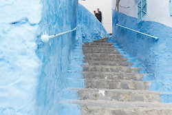 People walking past blue staircase, Chefchaouen, Morocco