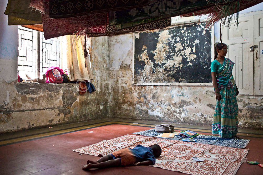 A child sleeping during class at the Kamatipura Centre in Mumbai. The centre welcomes about 100 children every day from the surrounding red-light district.<br /> The centre is run by the Prerana organisation who specialise in children of the red-light districts in Mumbai.