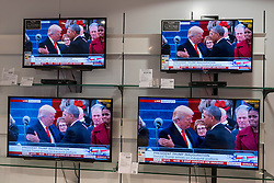 © Licensed to London News Pictures. 20/01/2017. London, UK. Outgoing President, Barack Obama, shakes hand with incoming President, Donald Trump.  Multiple TV screens in a department store show the live broadcast of the inauguration of Donald Trump as U.S. President.   Photo credit : Stephen Chung/LNP