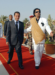 French President Nicolas Sarkozy is welcomed by Libyan leader Moammar Gadhafi upon his arrival in Tripoli, Libya on July 25, 2007. France and Libya on Wednesday signed a memorandum of understanding to build a Libyan nuclear reactor for water desalination and clinched a raft of other deals. Photo by Christophe Guibbaud/ABACAPRESS.COM