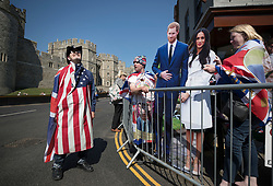 © Licensed to London News Pictures. 15/05/2018. Windsor, UK. Royal fans, who are the first to camp out on the procession route in Windsor High Street, display a life size cardboard cut out of the royal couple as they talk to a tourist draped in an American flag - ahead of the marriage of Prince Harry and Meghan Markle on Saturday. Photo credit: Peter Macdiarmid/LNP