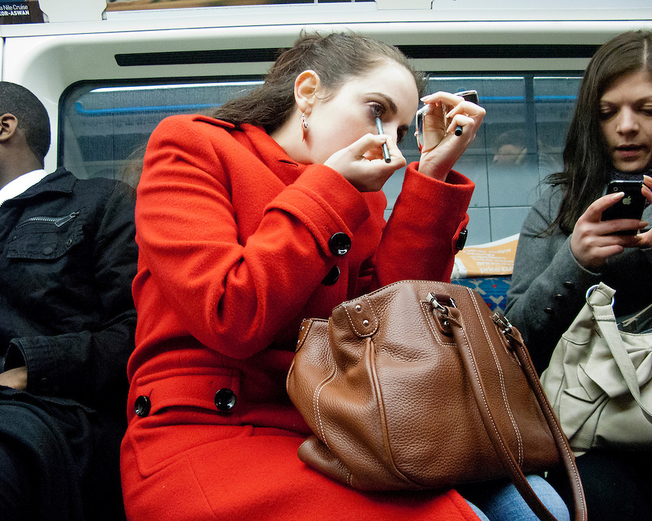 Female in red applying make-up getting ready on the London Underground