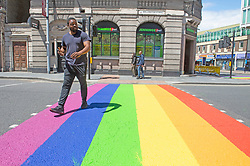 ©Licensed to London News Pictures 16/06/2020<br /> Woolwich, UK. A man walking on a colourful crossing in Woolwich town centre, Woolwich. Rainbow pedestrian crossings return to Greenwich Borough to show support for Gay pride month. Crossings in Eltham,Greenwich, plumstead,Charlton and Woolwich have had a rainbow make over bringing some colour to the streets in South East London. Photo credit: Grant Falvey/LNP