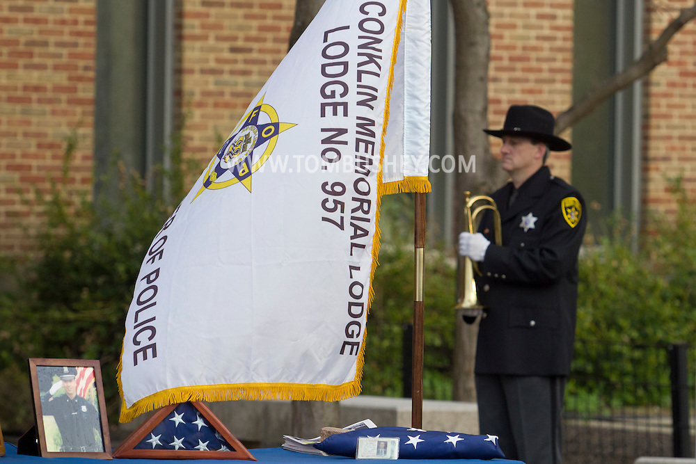 Goshen, New York - A portrait of a fallen police officer and American flags were on a table during the Orange County Law Enforcement Officer Memorial Service in front of the county courthouse on May 2, 2014. The memorial service honors the memory of the 27 members of the Orange County law enforcement community that died in the line of duty. The service also pays tribute the families and loved ones left behind for their courage, dignity and perseverance.