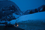 A car with headlights illuminating a high snow wall pulls out of an empy parking lot at night at Snoqualimie Pass, Washington.