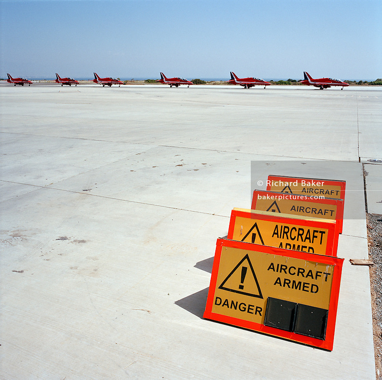 BAE System Hawks of the Red Arrows, Britain's RAF aerobatic team and airfield signs landscape.