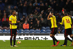 Watford's Marvin Zeegelaar (left) reacts after being shown a red card by referee Lee Probert (right) during the Premier League match at Turf Moor, Burnley.