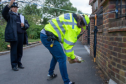 © Licensed to London News Pictures. 07/06/2020. London, UK. A police officer places flowers left by a friend inside the cordon at Fryent Country Park. The bodies of two women have been found in Fryent Country Park in Wembley. Metropolitan Police Service were called at 13:08 BST, Oficers found two unresponsive woman, they were pronounced dead at the scene. Photo credit: Peter Manning/LNP