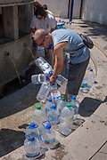 Using recycled bottles, locals collect thermal spring water at Fonte de Sao Joao, on 17th July 2016, in the spa resort of Luso, Portugal. In the 11th century, Luso was a sleepy village linked to a monastery in the hills near Coimbra but it became a lively spa resort in the 1700s as its hot water springs became a focus for tourism. The waters here are said to have therapeutic value in the treatment for bad circulation, muscle tone, rheumatism and renal problems.