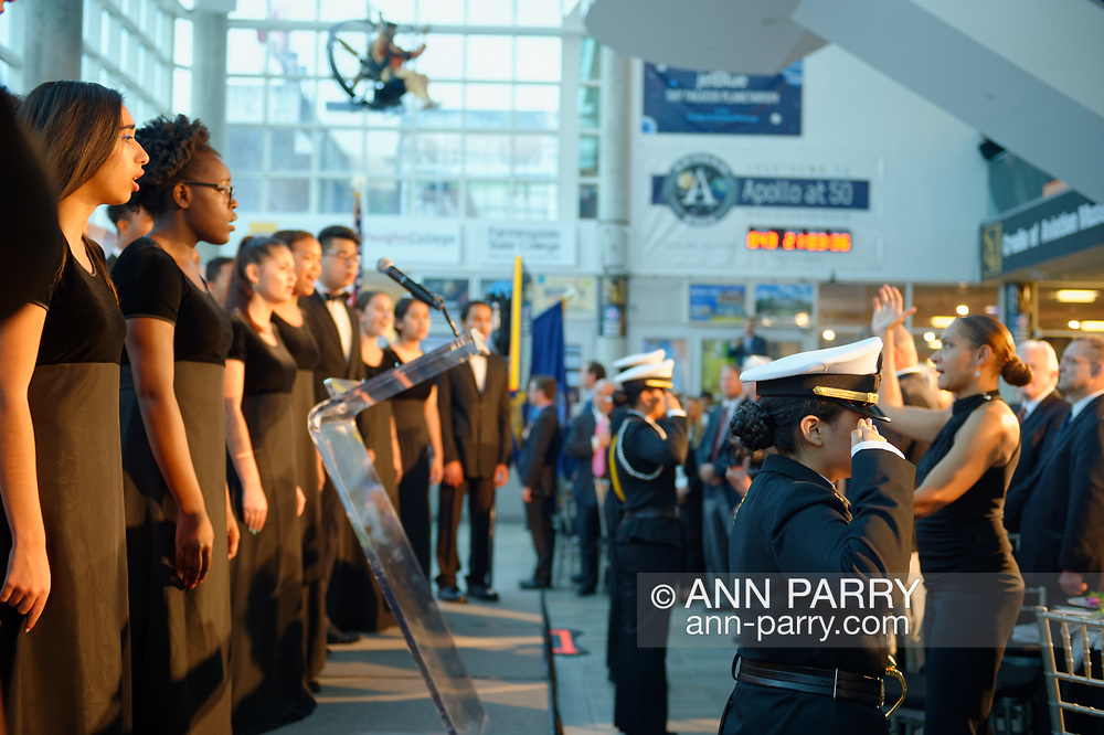 Garden City, NY, U.S. June 6, 2019. Freeport High School Select Chorale singers perform - with their Director MONIQUE CAMPBELL RETZLAFF standing at right, facing them - during Apollo at 50 Anniversary Dinner. FHS Navy Junior ROTC cadets are saluting. Apollo astronaut tribute celebrating the Apollo 11 mission Moon landing was held at Cradle of Aviation Museum.