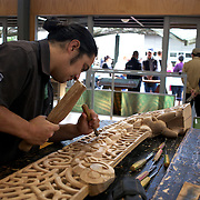 A man carving watched by tourists at Te Puia's Carving School, Rotorua, New Zealand,  New Zealand. .Te Puia is the premier Maori cultural centre in New Zealand - a place of gushing waters, steaming vents, boiling mud pools and spectacular geysers. Te Puia also hosts National Carving and Weaving Schools and  daily maori culture performances including dancing and singing. Rotorua, 9th December 2010 New Zealand.  Photo Tim Clayton