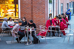 © Licensed to London News Pictures. 23/04/2021. Manchester, UK.  Diners wear red blankets to keep themselves warm as they sit in a dining area outside a restaurant . Following a day of sunshine , crowds of people fill Cutting Room Square on a Friday night in Ancoats , in the north of Manchester City Centre , as bars and restaurants reopen for outdoor service , following a loosening of Coronavirus controls . Photo credit: Joel Goodman/LNP