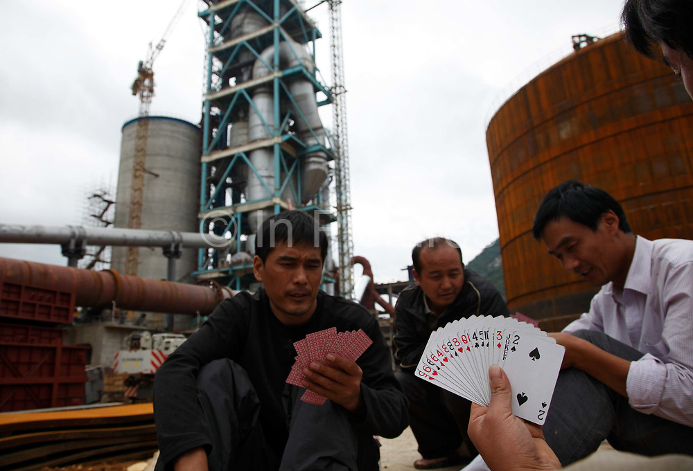 Truckers play cards while waiting for orders on the construction site of the soon to be finished Huaxin Cement Factory in Daoxian County, Hunan Province, China, on 03 June, 2010.  The large circular cement  structure will become the base of a large cement storage silo. The proliferation of heavy industry into every corner of China's countryside as a result of government stimulus has created an over capacity for materials such as cement and steel.