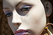 The face of a female manequin or showroom dummy with sunlight falling across her face.