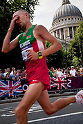 London, UK. Sunday 12th August 2012. Men's marathon competitor shows his fatigue as he passes St Pauls Cathedral through the City of London, the last of the track and field competitions in the London 2012 Olympics.