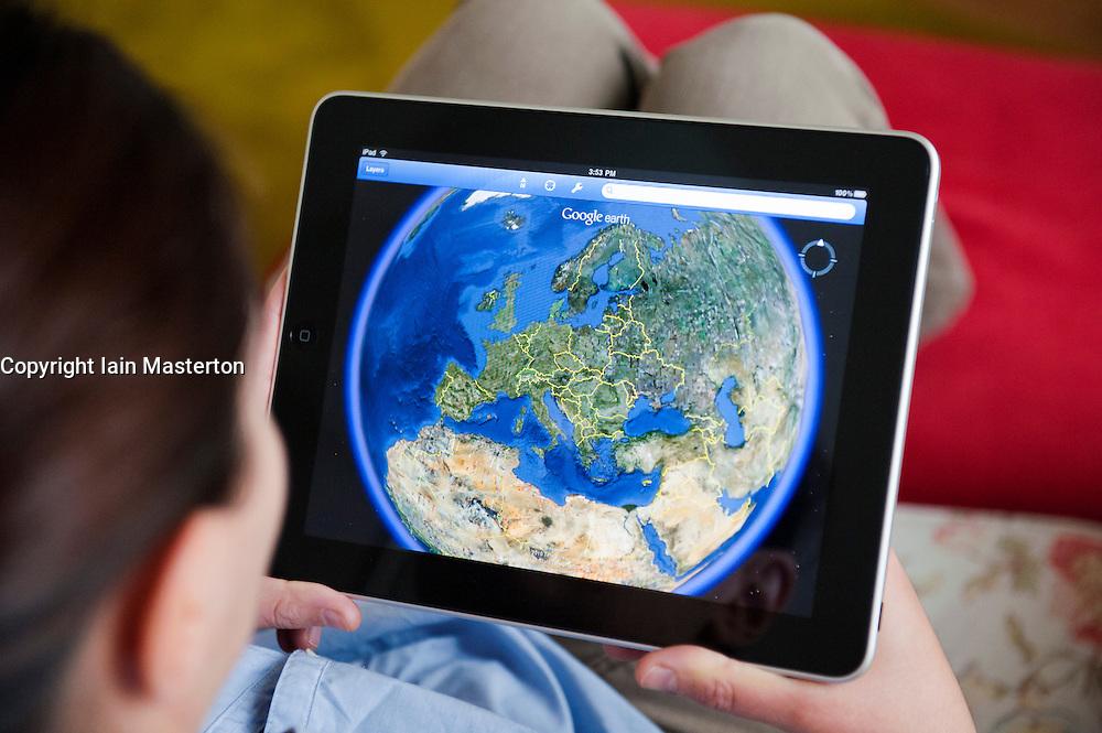 Woman using Google Earth application on iPad tablet computer