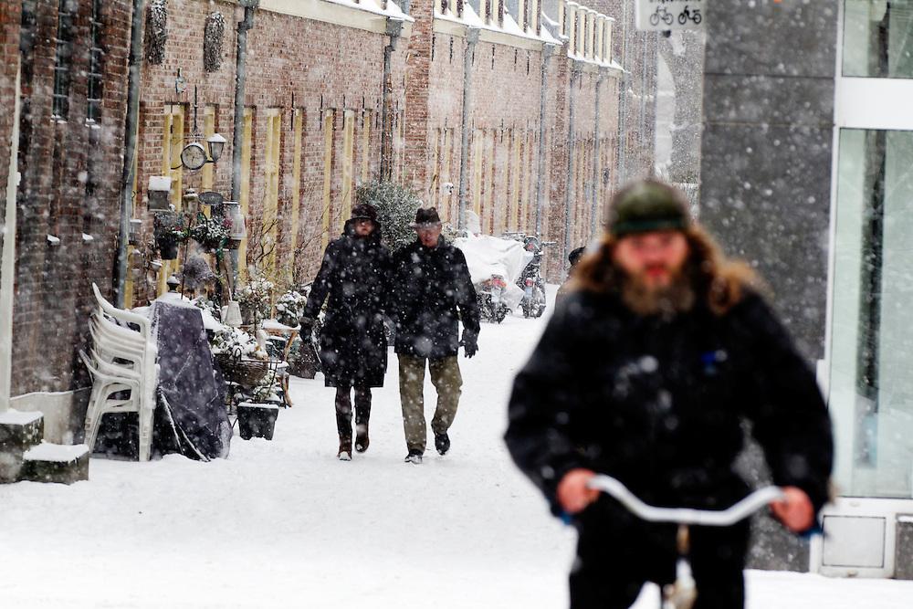 Een man en een vrouw lopen door de binnenstad van Utrecht in de sneeuw.<br /> <br /> A man a woman are walking in the snow.