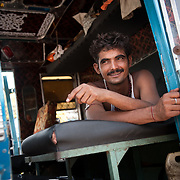 A truck driver rests in th cabin of his truck outside Haridwar, India, September 2009